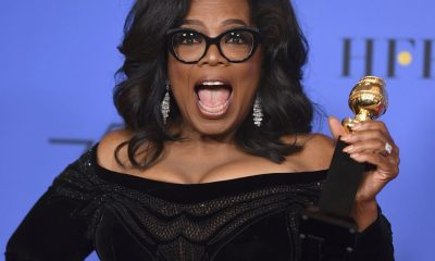 Oprah Winfrey holding up Golden Globe award